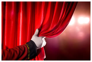 White gloved hand pulling back red theatre curtain1372012162644